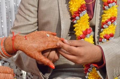 Intricate mehendi designed hands adorning a diamond studded wedding ring