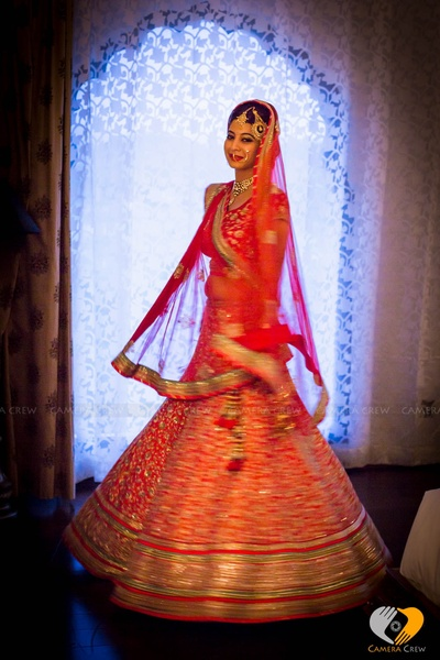 Bride decked in blood red wedding lehenga adorned with pom poms