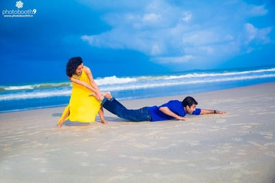 Funny pre wedding photo shoot by the beach dressed in smart casual outfits