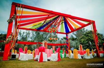 Colorful draped tent and bright and vibrant table chair setting at the mehendi ceremony.