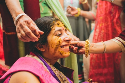 Bride's face filled with haldi for the haldi ceremony.
