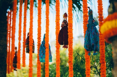 Mehendi decor with marigold and hanging puppets