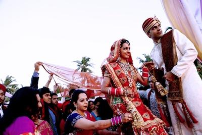 Red wedding lehenga bejweled with diamond studded regal bridal set  including neckpiece, raanihaar, maangtikka, haathphool and dangling earrings