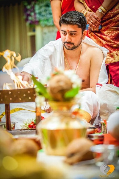 Groom covered in a white Angavastram is performing wedding rites