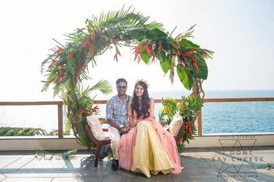 the bride and groom under a leafy wreath at the hawaaiin party