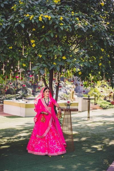 The bride in a fuschia pink lehenga by Sabyasachi for her wedding