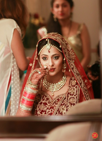Wearing regal red and gold bridal lehenga with heavy gold zardozi work paired with kundan jewellery.