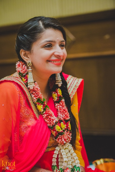 Dressed in a combination of red and yellow adorned with tasseled moti earrings and a fresh flower garland for the haldi ceremony