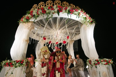 Outdoor wedding mandap decorated with chandelier, carnation topiaries and strings
