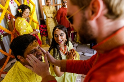 Friends smearing the groom with haldi
