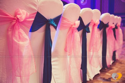 Chair arrangement for sangeet function, white covers for chair and pink and blue tie backs