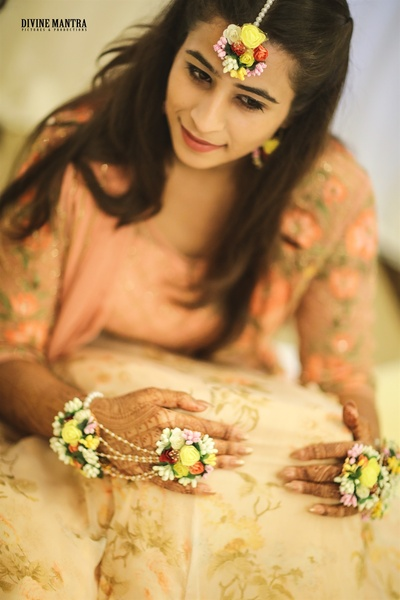 the bride in nude and peach lehenga with floral jewellery for her haldi ceremony