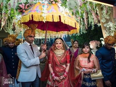 Bridal entry under the floral umbrella to her wedding venue
