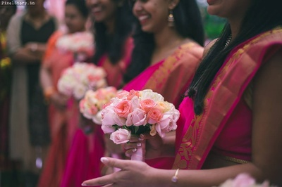 Bridesmaids holding pretty pink roses for the wedding ceremony.