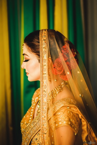 side portrait of the beautiful bride in a golden-yellow lehenga with roses in her hair