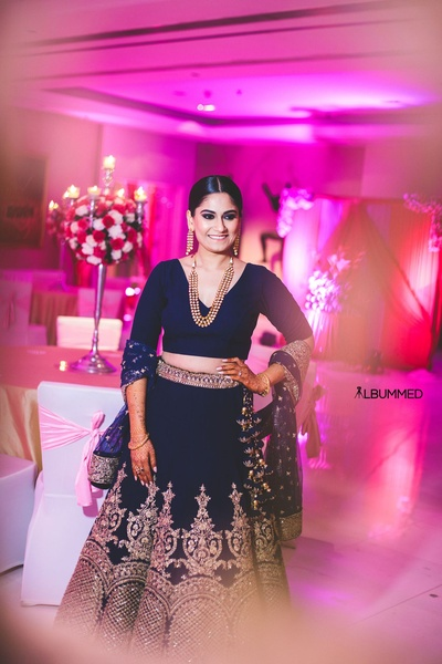 Dressed up in a royal blue lehenga with heavy gold zardozi work styled with minimal jewellery and makeup for sangeet ceremony.