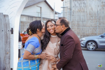 Candid capture of the bride with her parents during the engagement ceremony