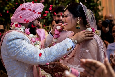 a candid capture of the bride and groom during the jaimala