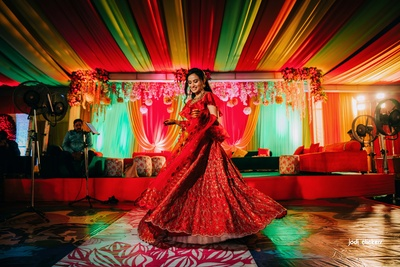 The bride looks stunning in this maroon gown with ruffles at her mehendi ceremony!