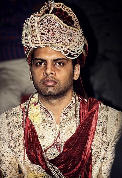Off white Sherwani teamed with a velvet Dushala and dazzling Safa