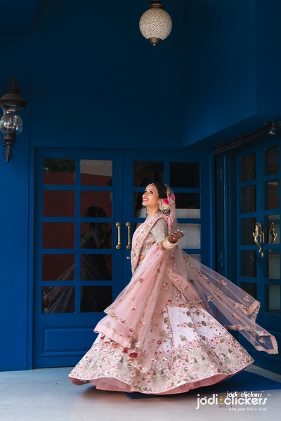 The stunning bride twirling in a baby pink lehenga with small embellishments!
