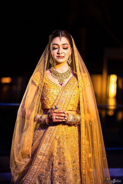 the beautiful bride in golden-yellow  embellished  lehenga for her wedding