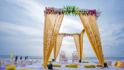 Gold draped mandap setup adorned with clustered floral arrangement