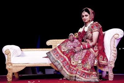 Heavily embellished red wedding lehenga with paisley and floral patterned embroidery stone work and gold zari borders