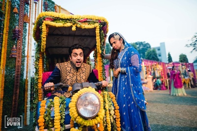 Bride and groom in a quirky pose with the decor of their summer wedding at Hotel Renaissance, Lucknow