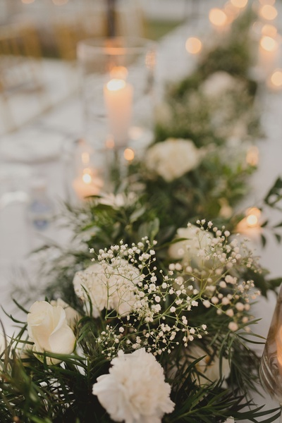 The dinner tables were decorated with white roses, foliage and baby breaths.