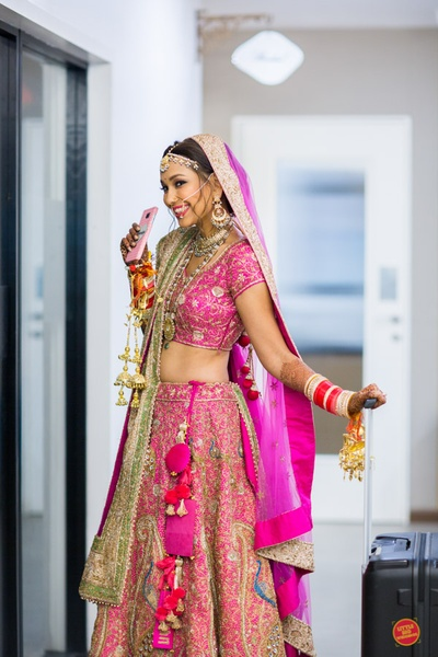 Bride Ratica stirkes a pose in her  fuschia pink lehenga with quiry customisations
