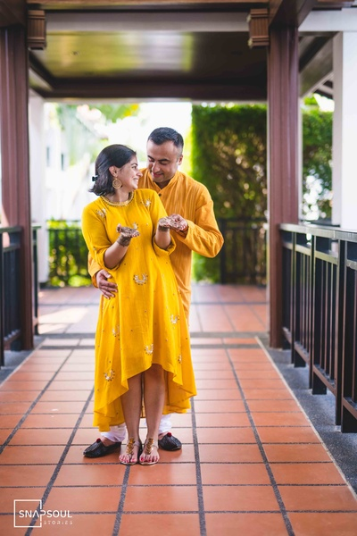 The couple twinning in different shades of yellow at the mehendi ceremony.
