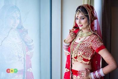 Bridal red lehenga-choli embellished with swirl patterned gol embroidery and velvet border