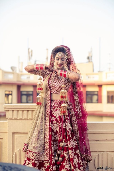 Dressed up in regal red and gold bridal lehenga  by Sabyasachi styled with kundan jewellery and gold kaleere.