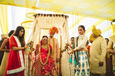 Unique bridal entry ideas for the couple. Floral canopy for the bride's entry to the phera mandap