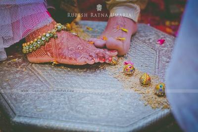 Three-strand anklet with gold pearls, kundan and meenkari beads adorned on intricately designed mehendi feet