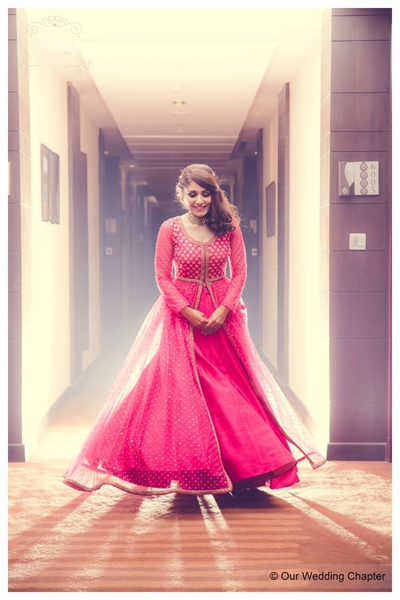 Red flared anarkali dress with an embellished bodice and a simple loose hairstyle