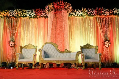 Fresh flower curtain-style decor lit up in soft lighting, beautifying the classy gold and white seating