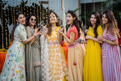 the bride and her bridesmaids at the haldi ceremony