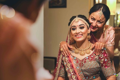 Mother of the bride helps her get ready for the wedding ceremony