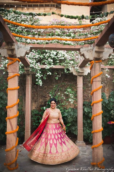 Wearing pink and gold bridal lehenga by Frontier Raas styled with minimal bridal jewellery.