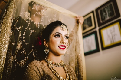 pretty bride getting ready for her wedding ceremony in a golden lehenga