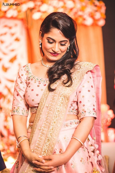 Dressed up in a peach and gold lehenga for engagement ceremony.