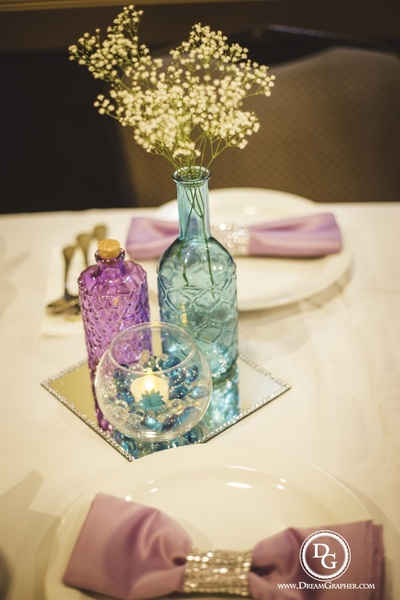 Purple and blue glass bottles adorned with baby breath flowers