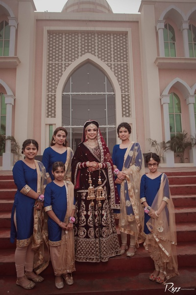 The bride poses  with her cute bridesmaids