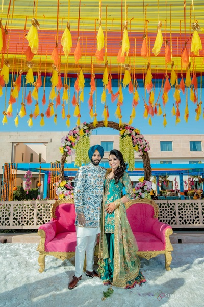 The bride and groom look super duper gorgeous in their blue outfits, posing in front of a large floral wreath.