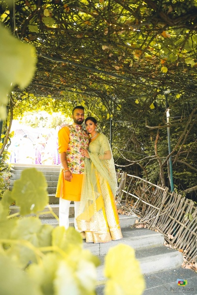 Bride and groom pose together in yellow and gold lehenga nad sherwani for the reception