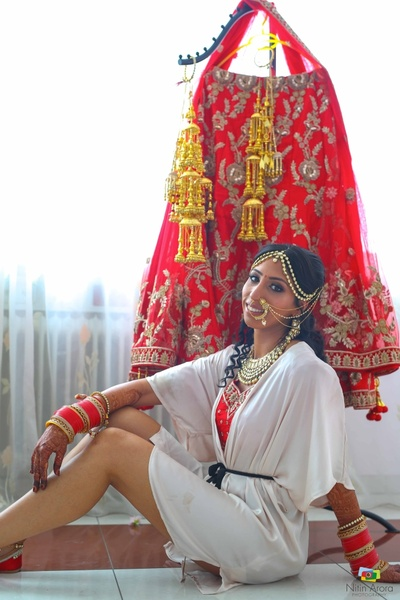 Bride poses with her red lehenga and gold kalire for the wedding ceremony