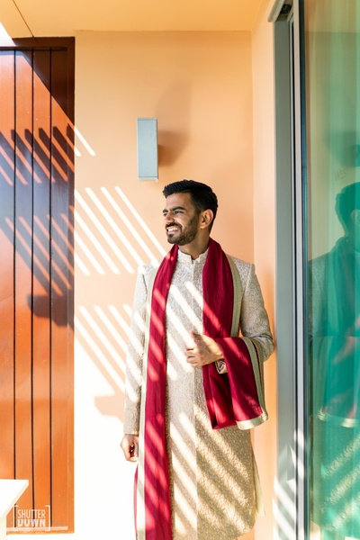 The groom in an ivory sherewani with red dupatta for his wedding