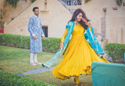 Twirling around for a candid pre wedding photo shoot dressed in yellow and blue bright hues